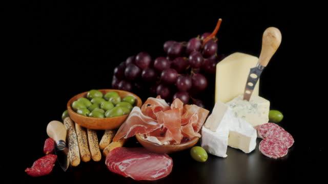 vídeos de stock e filmes b-roll de antipasto with cheese, grapes and olives rotates. - cortar atividade