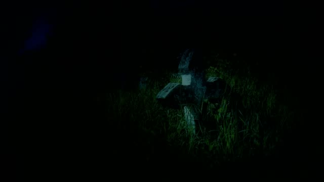 Antique cemetery graveyard at night with a stone cross overgrown with grass