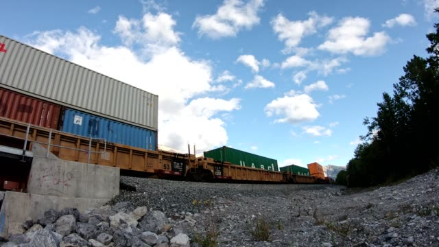 Video Antique train long freight with container loading running on railway passing  in valley at Calgary