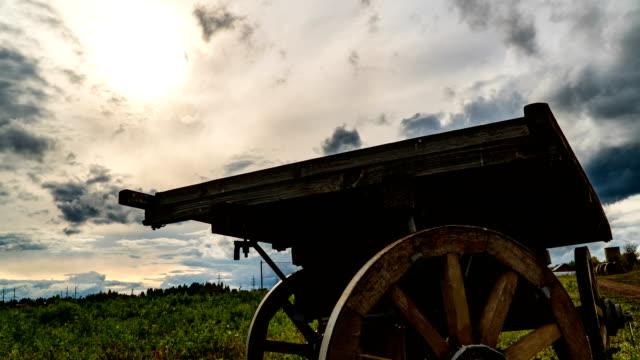 Antique wooden cart standing alone in a field, beautiful autumn landscape, hyperlapse, time lapse, heavy autumn sky