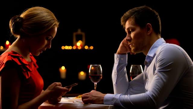 vídeos de stock e filmes b-roll de anxious man looking at female scrolling smartphone on date, replacing reality - namorar