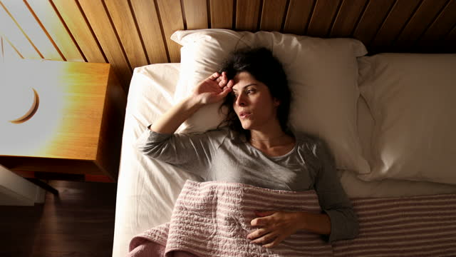 Anxious single woman in bed suffering before sleep