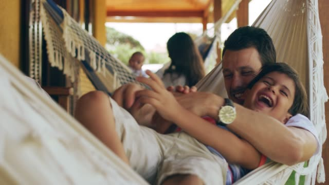Anything to hear him laugh 4k video footage a father tickling his adorable son on a hammock outside brazil stock videos & royalty-free footage