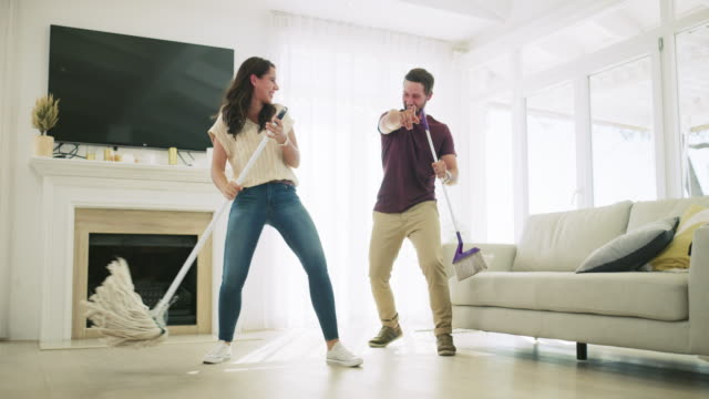 Anywhere can be a dance floor 4k video footage of an affectionate young couple singing and dancing while cleaning their living room at home chores stock videos & royalty-free footage