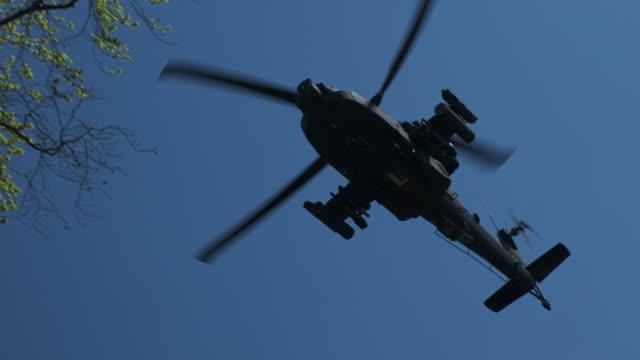 木々の上を低空飛行するオランダ国防軍のアパッチヘリコプター - ヘリコプター点の映像素材/bロール