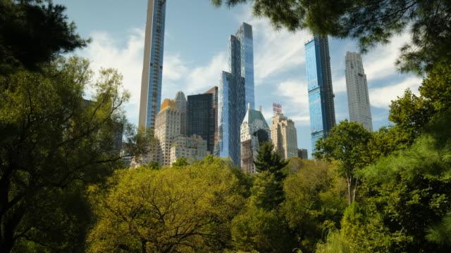 vídeos de stock e filmes b-roll de apartment and condominium skyscraper residences rise up over the manhattan skyline in central park in new york city usa - elegante