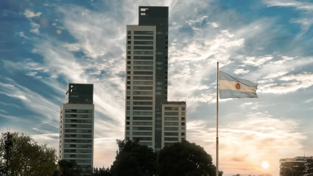 apartment building and argentine flag at sunset, in buenos aires, argentina. - bandiera dell'argentina video stock e b–roll