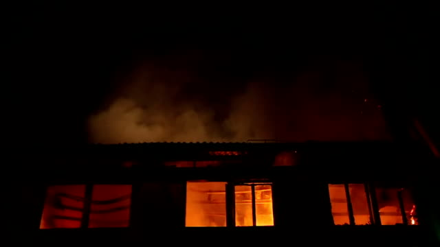 apartment building on fire at night time - incendio doloso video stock e b–roll