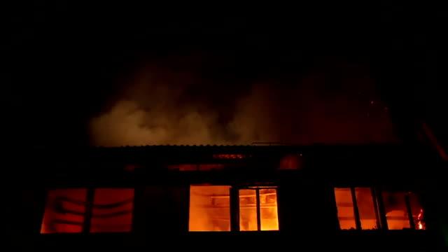 vídeos de stock e filmes b-roll de apartment building on fire at night time - labareda