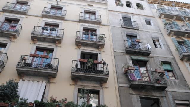 バルセロネタ地区集合住宅街。バルセロナのゴシック地区にバルコニーのある家。ファサードは、バルセロナの狭い通りの古民家します。旅のコンセプトです。スローモーション - 建物の正面点の映像素材/bロール