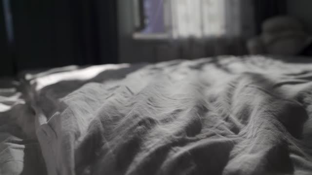 vídeos y material grabado en eventos de stock de interior del apartamento, dormitorio a la sombra con cama sin hacer, ventana abierta - dormitorio habitación