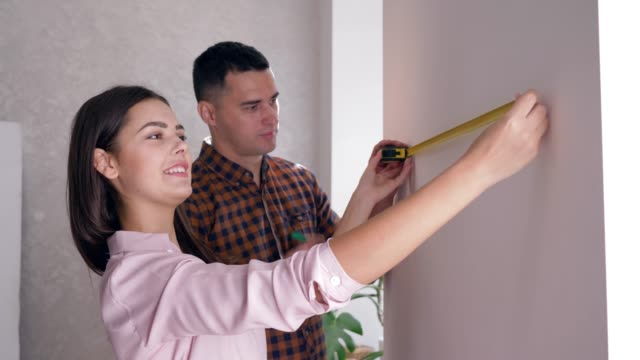 apartment repair, young woman and man with tape measure in hand doing renovation in new housing apartment repair, young woman and man with tape measure in hand doing renovation in new housing close-up renovation stock videos & royalty-free footage