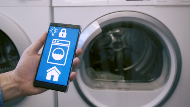 IOT app controls household appliances in home like washing machines Concept of internet of things (IOT). Smart home automation of washing machine controlled by app on mobile phone. The app on the screen is not real. It is made in After Effects by me. Property release attached. appliance stock videos & royalty-free footage