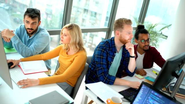app developers at the office. - продвижение трудовые отношения стоковые видео и кадры b-roll