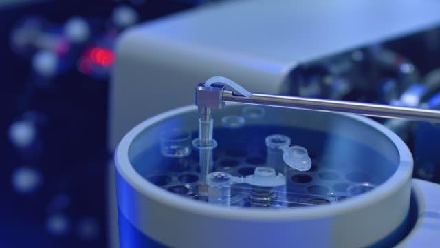 vídeos de stock, filmes e b-roll de aparelho para amostragem automática, análise. uma mão robo tira uma amostra de um tubo de ensaio para testes ou análises. novas tecnologias na ciência. inteligência artificial está conduzindo um experimento - exatidão
