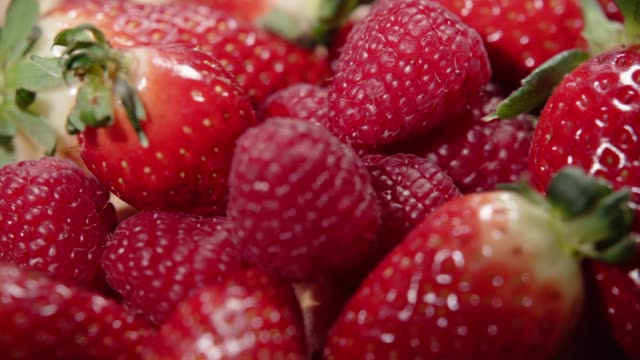 vídeos de stock e filmes b-roll de appetizing and beautiful red strawberries and raspberry. red ripe organic strawberries on the market. 4k - framboesa