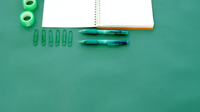 Apple and office supplies on green background 4k video