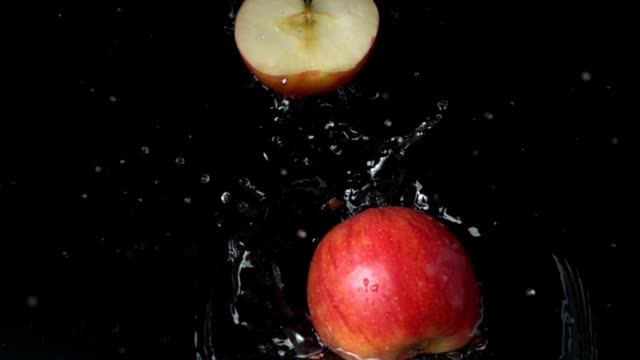 Apple falls in water. Slow motion.