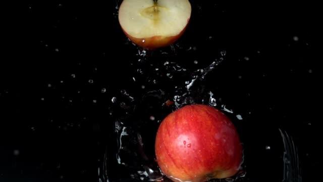 apple falls in water. slow motion. - jabłko filmów i materiałów b-roll