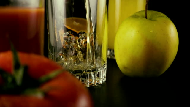 Apple juice is poured into one of the three glasses on the table. Slow mo video