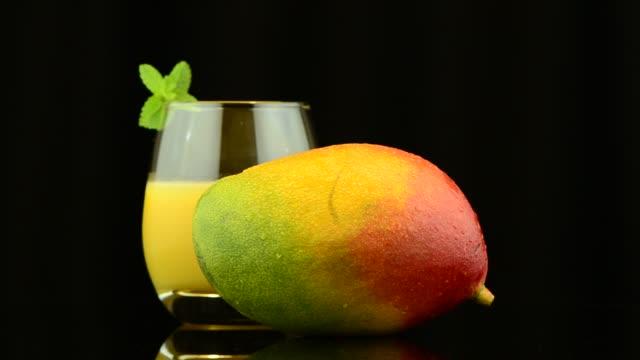 Apple mango Apple mango and juice rotating on black background. mango stock videos & royalty-free footage