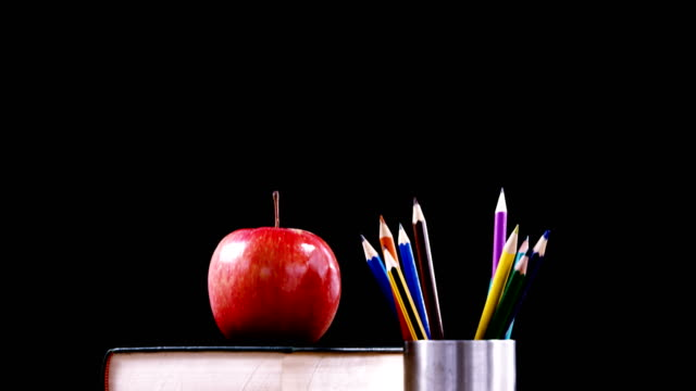 Apple on book stack with color pencil on table video