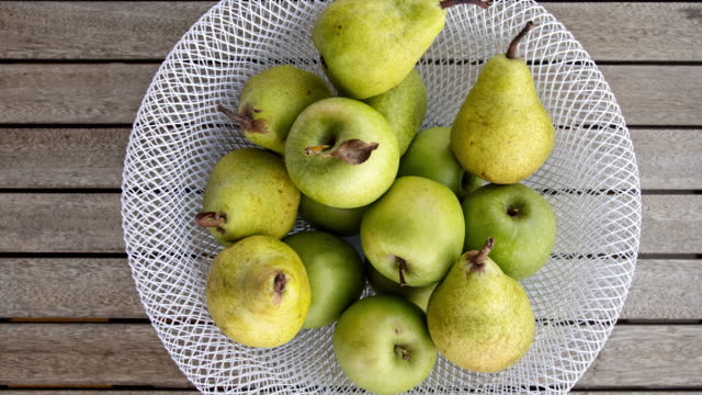 vídeos de stock e filmes b-roll de apples and pears in decorative bowl on wooden table - saladeira