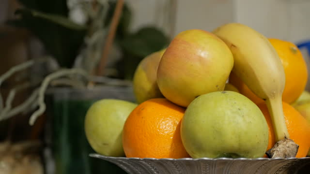 Apples, bananas and oranges are on a plate. Fresh juicy fruits are on a plate