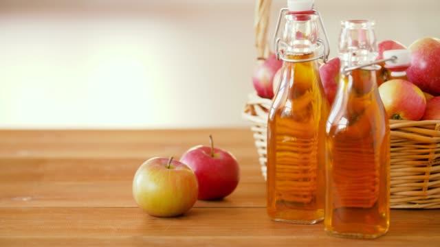 사과 바구니와 테이블에 주스의 병 - 식초 스톡 비디오 및 b-롤 화면