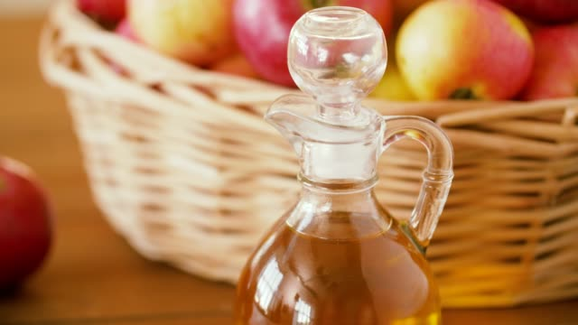 사과 바구니에 주스 또는 테이블에 식초의 용기 - 식초 스톡 비디오 및 b-롤 화면