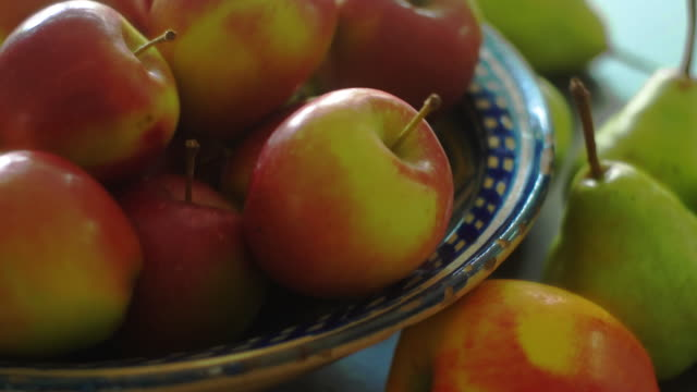 Apples & pears Close up dolly shot of apples & pears in a rustic bowl, backlit. pear stock videos & royalty-free footage