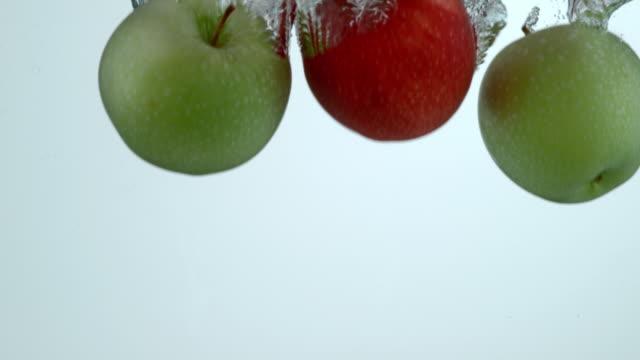Apples splashing into water in slow motion video