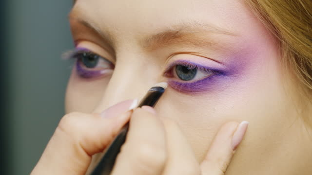 apply makeup on a beautiful female eye of blue color - make up stock videos & royalty-free footage
