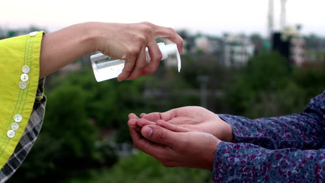 Aplicando o desinfetante de álcool na mão e lavando as mãos com sanitizador contra Coronavirus ou Covid-19. - vídeo