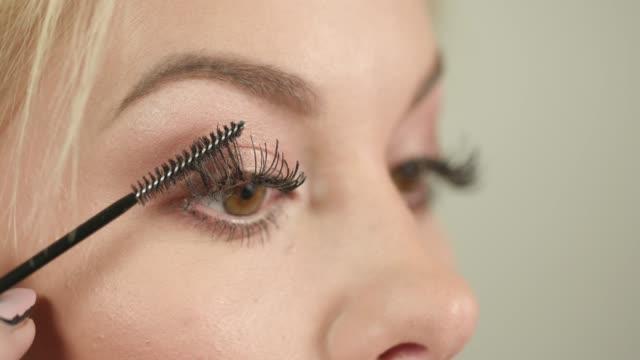applicering av svart mascara med applikatorn - makeup artist bildbanksvideor och videomaterial från bakom kulisserna
