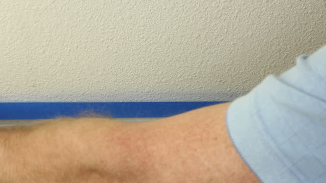 Applying Blue Painter's Tape to Prepare for Painting video