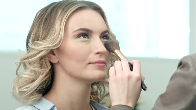 Applying blush makeup with brush to cheekbones of smiling young woman video