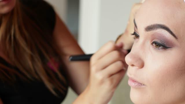 tillämpa rouge med make-up borste på modellens ansikte - makeup artist bildbanksvideor och videomaterial från bakom kulisserna