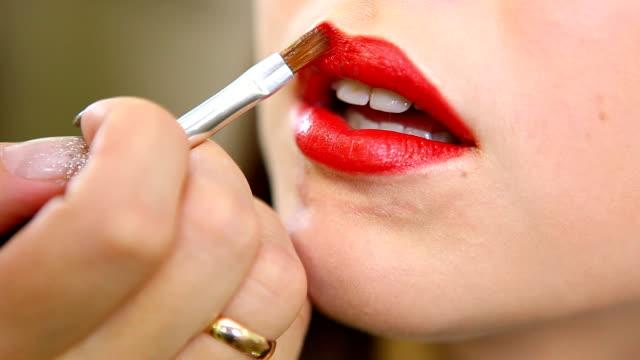applying bright red lipstick video