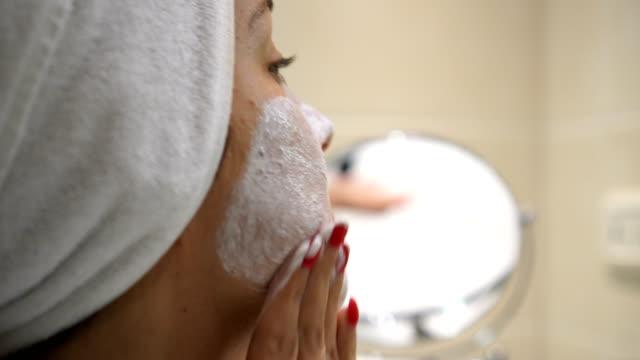 applying cream on face - viziarsi video stock e b–roll