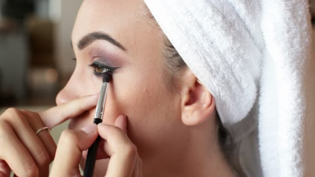 Applying eyeshadow with brush on beauty contest model's face Make-up artist applying eyeshadow on beauty contest model's face, using brush eyeliner stock videos & royalty-free footage
