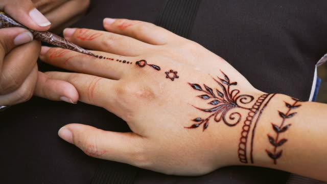 vídeos de stock e filmes b-roll de applying henna paint on fingers - mandala