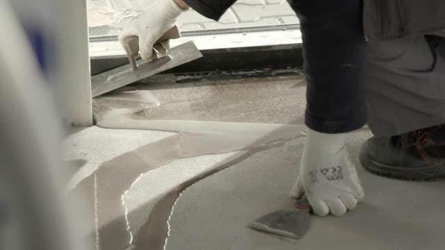 applying liquid resin on cracked cement floor - lucidare video stock e b–roll