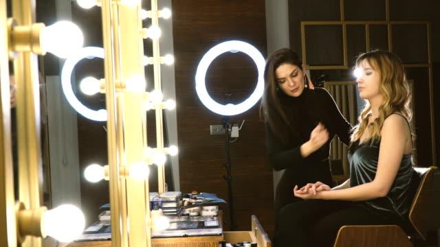 tillämpa make up på face av vacker kvinna - makeup artist bildbanksvideor och videomaterial från bakom kulisserna