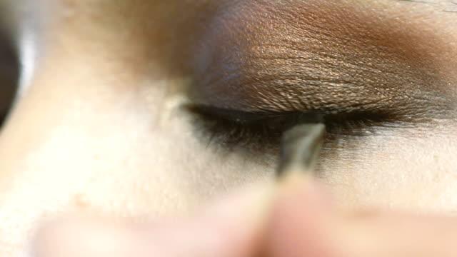 vídeos de stock e filmes b-roll de applying make up on face of beautiful woman - sombra para os olhos