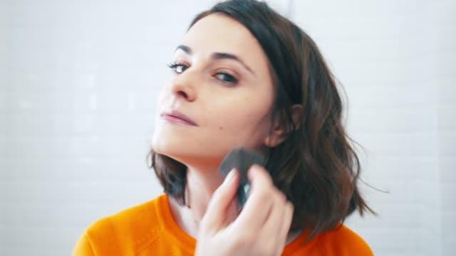 vidéos et rushes de appliquer la poudre de maquillage avec une brosse. - pinceau à maquillage