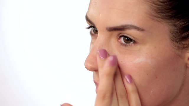 Applying moisturiser into face video