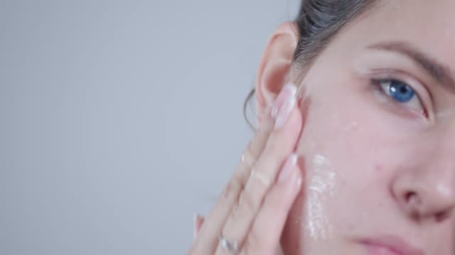 Applying peel off mask on face Young woman applying peel off mask on face, slow motion, close up-shot skin care stock videos & royalty-free footage
