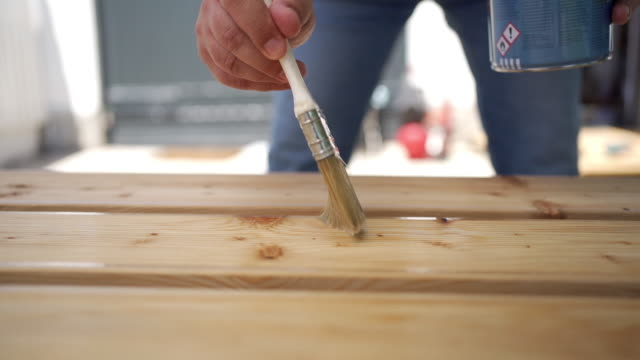 vídeos de stock e filmes b-roll de applying protective varnish on a wooden boards. - mesa mobília