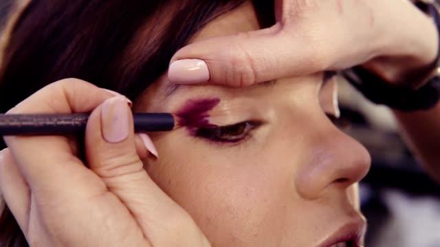 外側の隅とスモーキー目の完璧な外観を作成する外部の折り目で紫を適用するアイライナー。ヘーゼル ナッツの目のブルネット白人見ている女の子。 - アイシャドウ点の映像素材/bロール